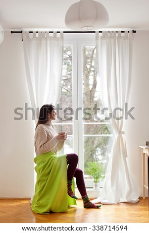 Beautiful young woman sitting by the window having hot drink - stock photo