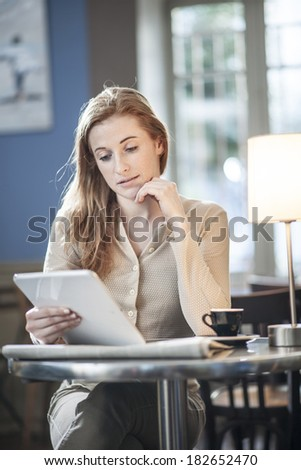 beautiful young woman sitting in a cafe and using a digital tablet