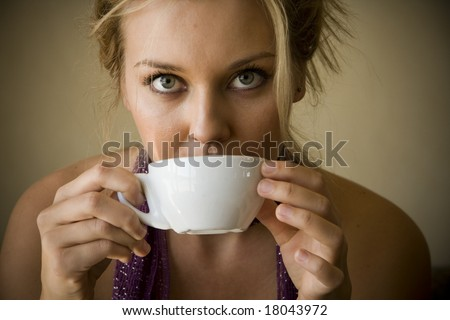 beautiful young woman sitting in a cafe drinking coffee