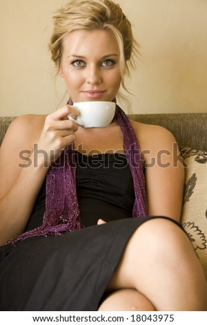 beautiful young woman sitting in a cafe drinking coffee - stock photo