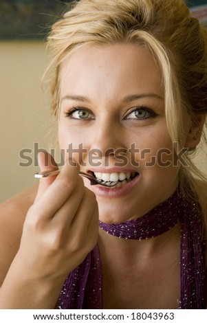 beautiful young woman sitting in a cafe eating cake - stock photo