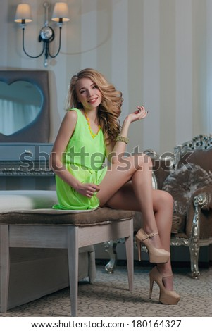 Beautiful young woman sitting in a trendy dress. Fashion photos.