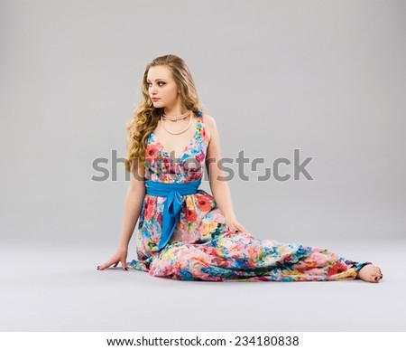 Beautiful young woman sitting in a trendy long dress - stock photo