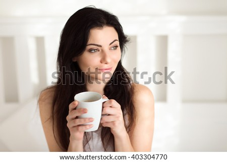 Beautiful young woman sitting in Bed in the Morning and drinking Coffee or Tea and enjoy a relaxing sunny sunday morning - stock photo