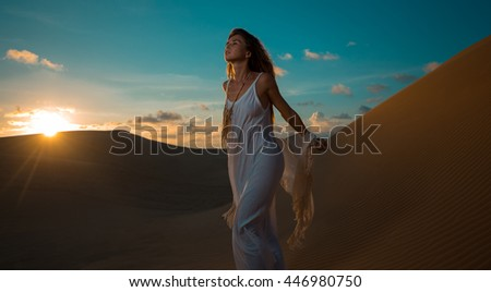 Beautiful young woman sitting in sandy dunes. Fashion style concept