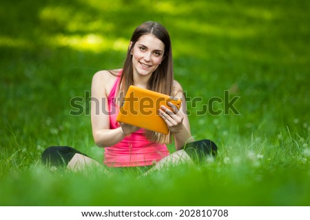 Beautiful young woman sitting in the park with tablet