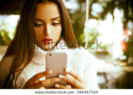 beautiful young woman sitting  in trendy urban coffee shop and texting message on her smartphone.  - stock photo