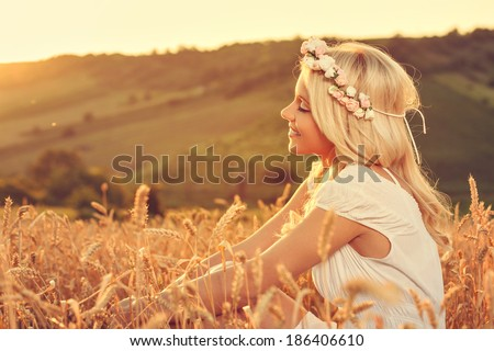 Beautiful young woman sitting in wheat and enjoy - stock photo