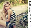 beautiful young woman sitting near bike - stock photo