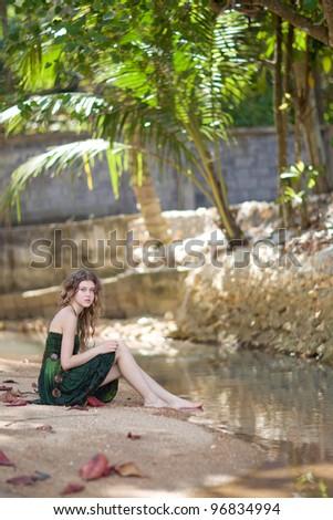 Beautiful young woman sitting near lake - stock photo