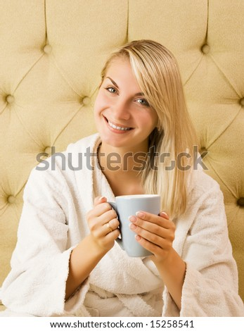 Beautiful young woman sitting on a bed and drinking coffee in the morning