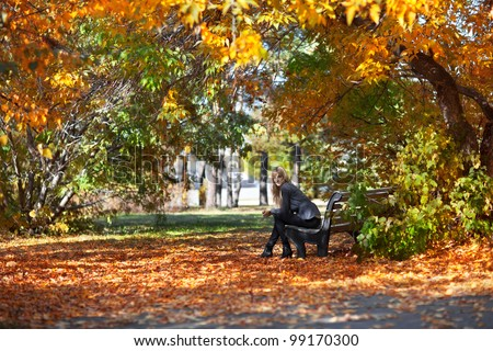Beautiful young woman sitting on a bench in autumn park - stock photo