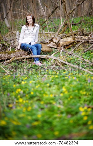 Beautiful young woman sitting on a branch in a spring park