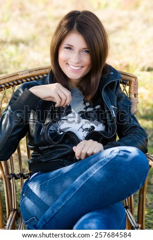 Beautiful young woman sitting on a chair outdoors. Beautiful smile on her face.
