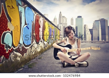 Beautiful young woman sitting on a city street and playing the electric guitar - stock photo