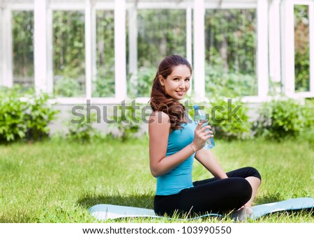 Beautiful young woman sitting on a green grass with bottle of water - stock photo