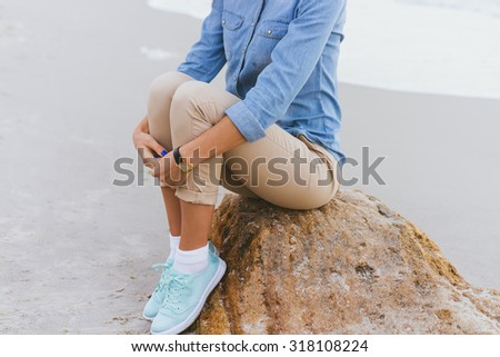 Beautiful young woman sitting on a rock by the sea. She is dressed in beige trousers and a denim shirt. Walking in the fresh air. - stock photo