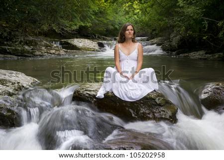 Beautiful young woman sitting on a rock surrounded by the purifying waters of a clear mountain stream - stock photo