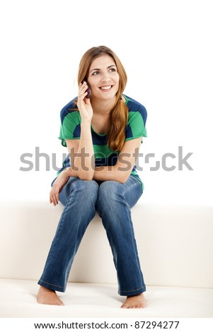 Beautiful young woman sitting on a sofa and making a phone call, isolated on white - stock photo