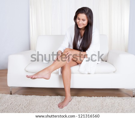 Beautiful young woman sitting on a sofa in her living room admiring her bare legs - stock photo