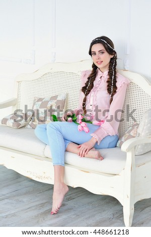 Beautiful young woman sitting on a vintage sofa, smiling happily and holding a bunch of delicate spring pink tulips - stock photo