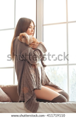 Beautiful Young Woman Sitting On A Windowsill And Playing With Easter Bunny