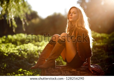 Beautiful Young Woman sitting on log posing - stock photo