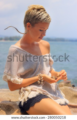 Beautiful young woman sitting on picturesque rocky seashore playing with shells - stock photo
