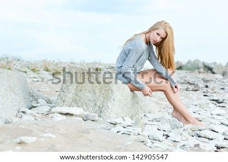Beautiful young woman sitting on rock