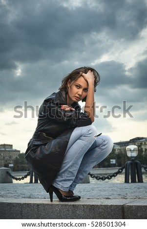 Beautiful young woman sitting on stone steps