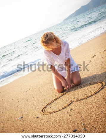 Beautiful young woman sitting on the beach and making heart shape in sand.  - stock photo
