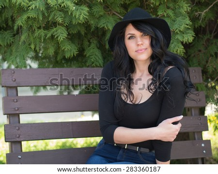 beautiful young woman sitting on the bench and looking at you