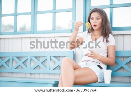Beautiful young woman, sitting on the bench, holding a fast food lunch box, eating up noodles from Chinese take-out with chopsticks and drinking takeaway coffee. - stock photo