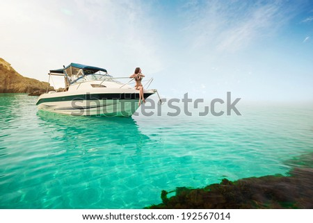 Beautiful young woman sitting on the boat a sunny summer day. Luxury vacation at sea. - stock photo