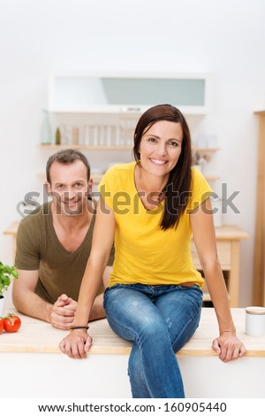 Beautiful young woman sitting on the counter top in the kitchen smiling at the camera with her husband leaning on the counter behind her