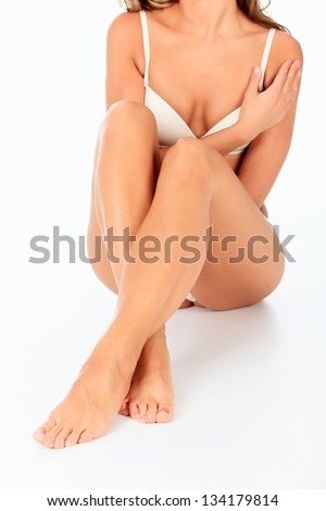 Beautiful young woman sitting on the floor - isolated on a white background - stock photo