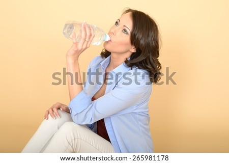 Beautiful Young Woman Sitting on the Floor Wearing a Blue Shirt and White Jeans Smiling Holding A Bottle of Still Mineral Water.