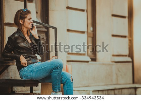 Beautiful young woman sitting on the stairs and talking on the phone - stock photo