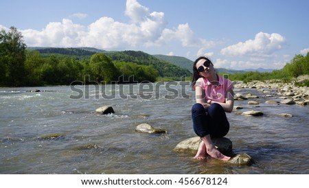 Beautiful young woman sitting on the stone in mountain river and smiling
