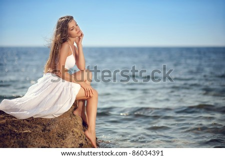 Beautiful young woman sitting on the stone on the seashore