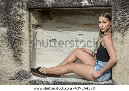 Beautiful young woman sitting on the wall - stock photo
