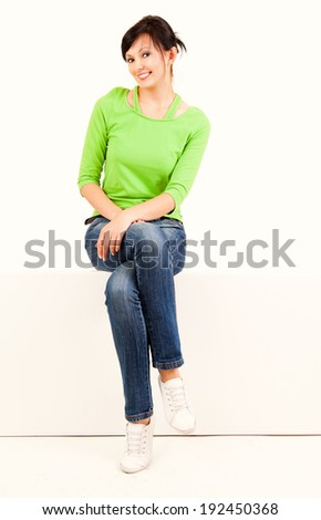 beautiful young woman sitting on the wall, full lenght, white background