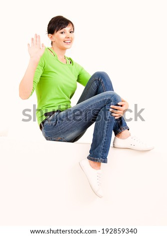 beautiful young woman sitting on the wall, full lenght, white background - stock photo