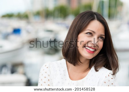 Beautiful young woman sitting outdoors at the coast looking up attentively towards the right of the frame with a smile as though listening to someone - stock photo