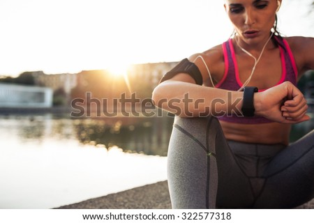 Beautiful young woman sitting outdoors using a smartwatch to monitor her progress. Caucasian female runner resting and checking her performance on fitness smart watch device. - stock photo