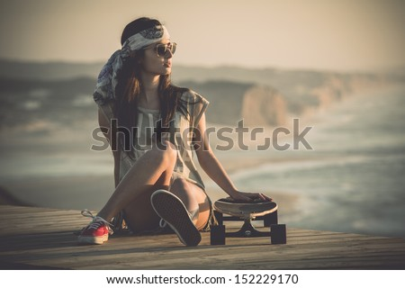 Beautiful young woman sitting over a skateboard - stock photo