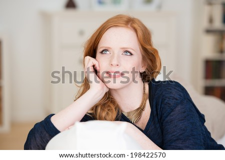 Beautiful young woman sitting thinking leaning over the back of a comfortable sofa staring up into the air with a contemplative expression - stock photo