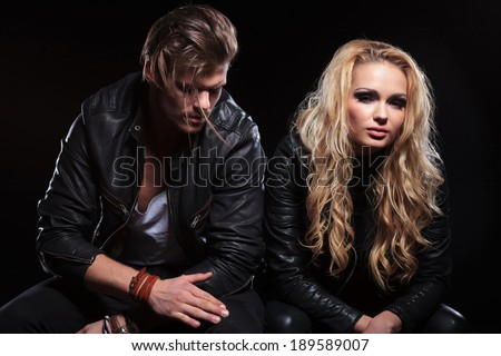beautiful young woman sitting with her boyfriend and looking into the camera . on black background