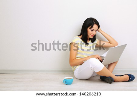 Beautiful young woman sitting with notebook in room - stock photo