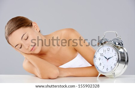Beautiful young woman sleeping alongside a classic retro alarm clock with bells sitting at a table with her head resting on her arm and a peaceful expression